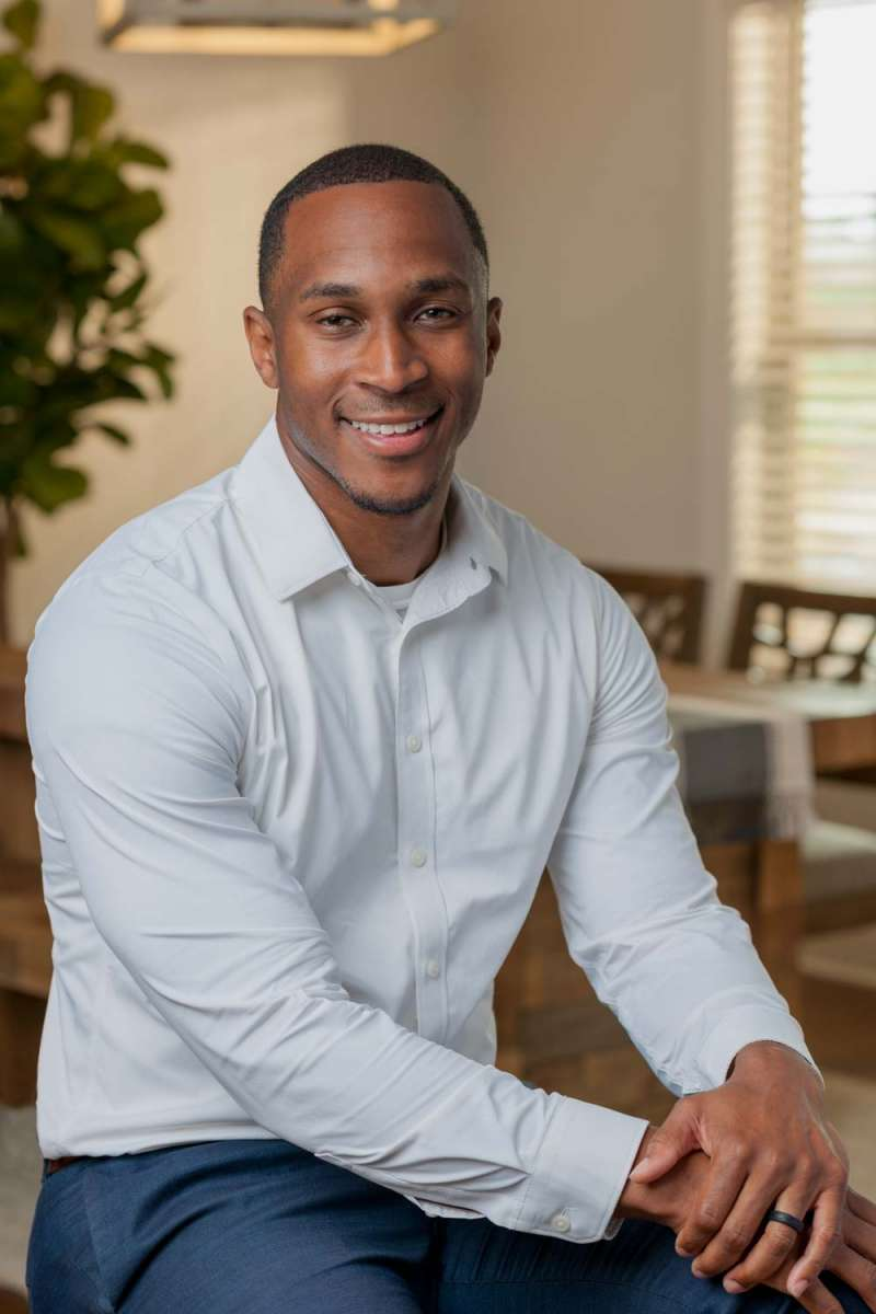 Headshot photograph of realtor Corey Gilmore wearing a white shirt. In the background is a dining table & chairs with a plant on the left side and a window on the right side.