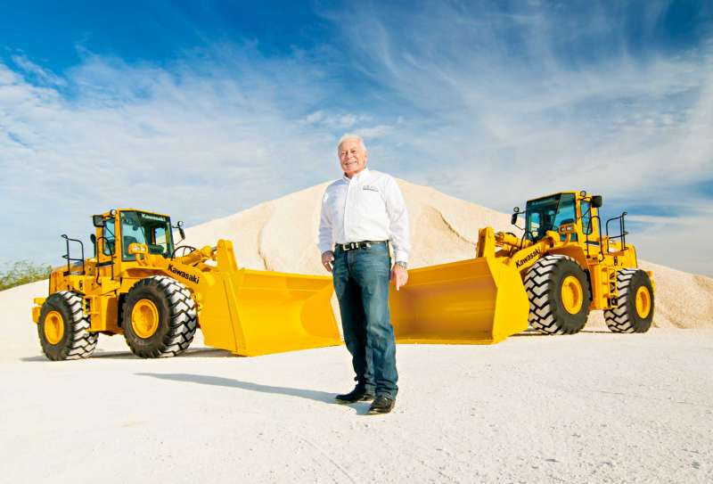 CEO portrait showing company owner standing in front of kawasaki tractors