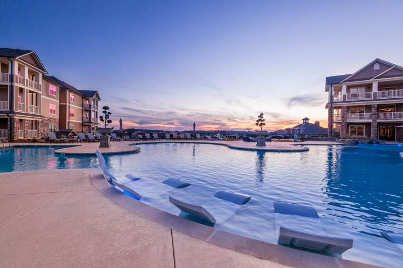 A beautifully designed residential swimming pool reflecting the sky in this real estate photograph.