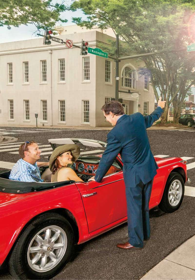 A commercial photograph showing a well-dressed fnancial advisor giving guidance to a couple traveling towards their retirement in an antique red MG.