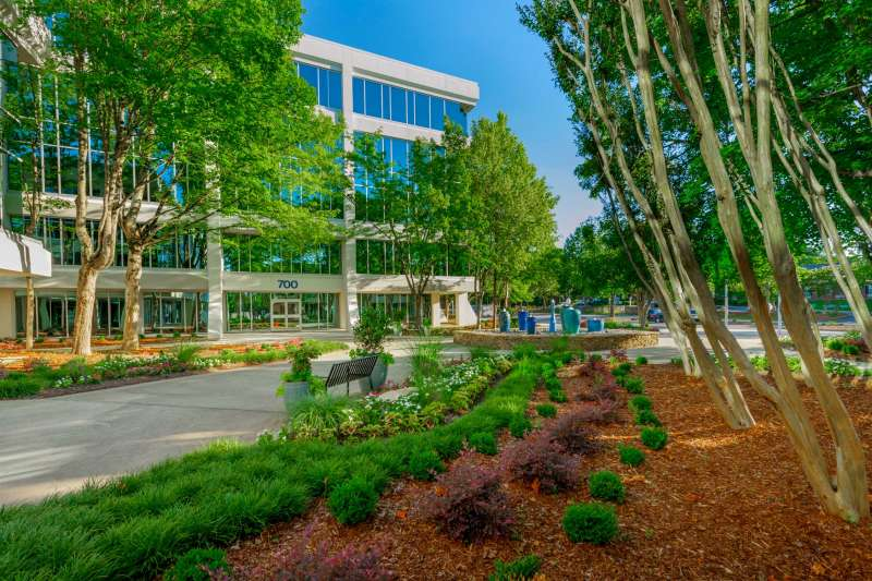Real estate photograph of showing a 5-story building exterior surrounded by trees and landscaped courtyard area.
