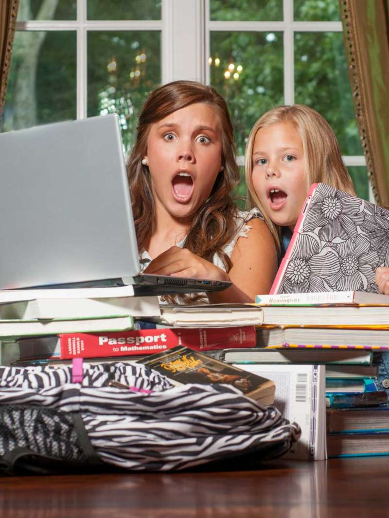 Photograph od two young women at home astounded by the amont of piled up school books and projects in front of them.