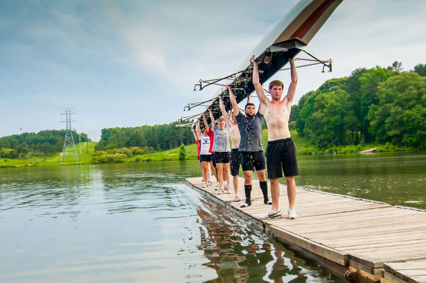 Editorial photography showing the UGA sculling crew lifting their boat out of the water.