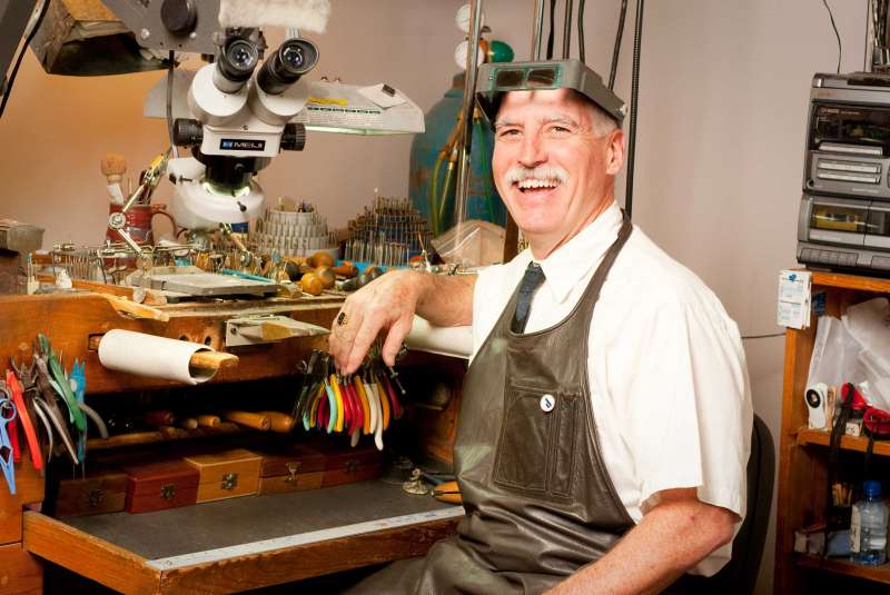 Editorial portrait of jeweler TK Anderson at his work bench.