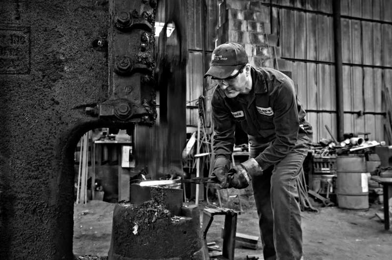Black and white environmental portrait of a tool maker hammering a hot piece of iron.
