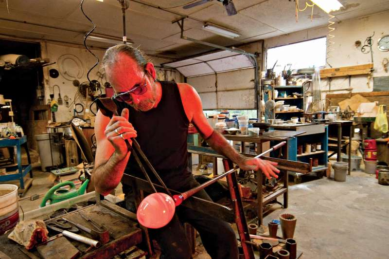 Photography for magazine article showing a glass blower crafting a vase in his workshop.