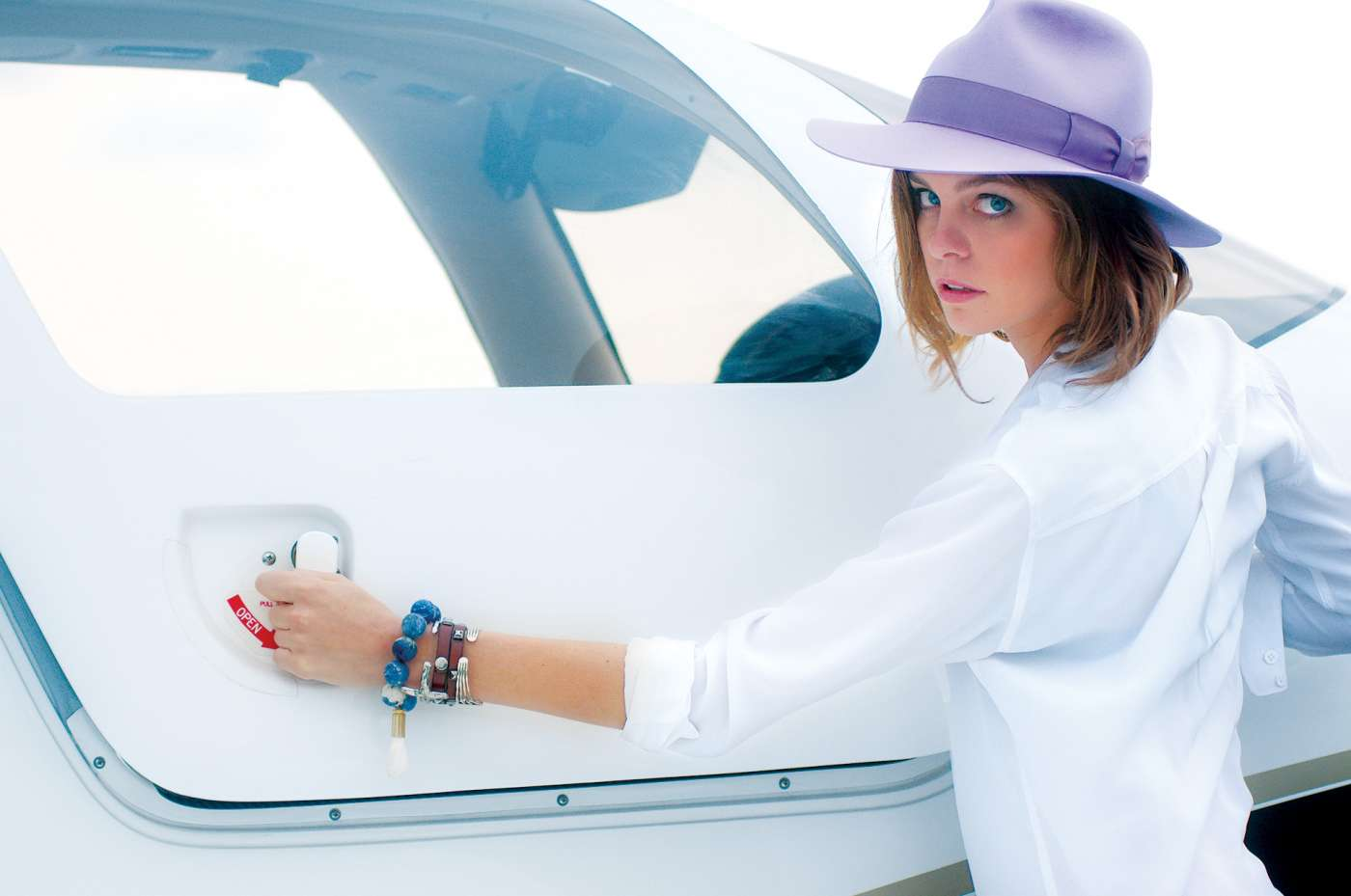 Fashion photography showing a beautiful woman opening an aircraft cockpit.