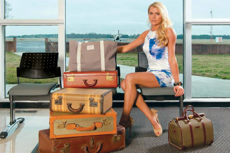 Fashion photographer JP Bond captures a stylish woman sitting in an airport with vintage luggag