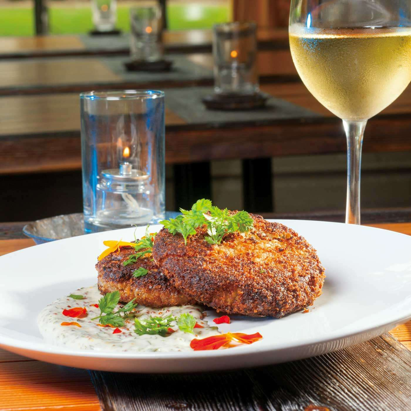 Cookbook photography of crab cakes with a sparkling glass of white wine.