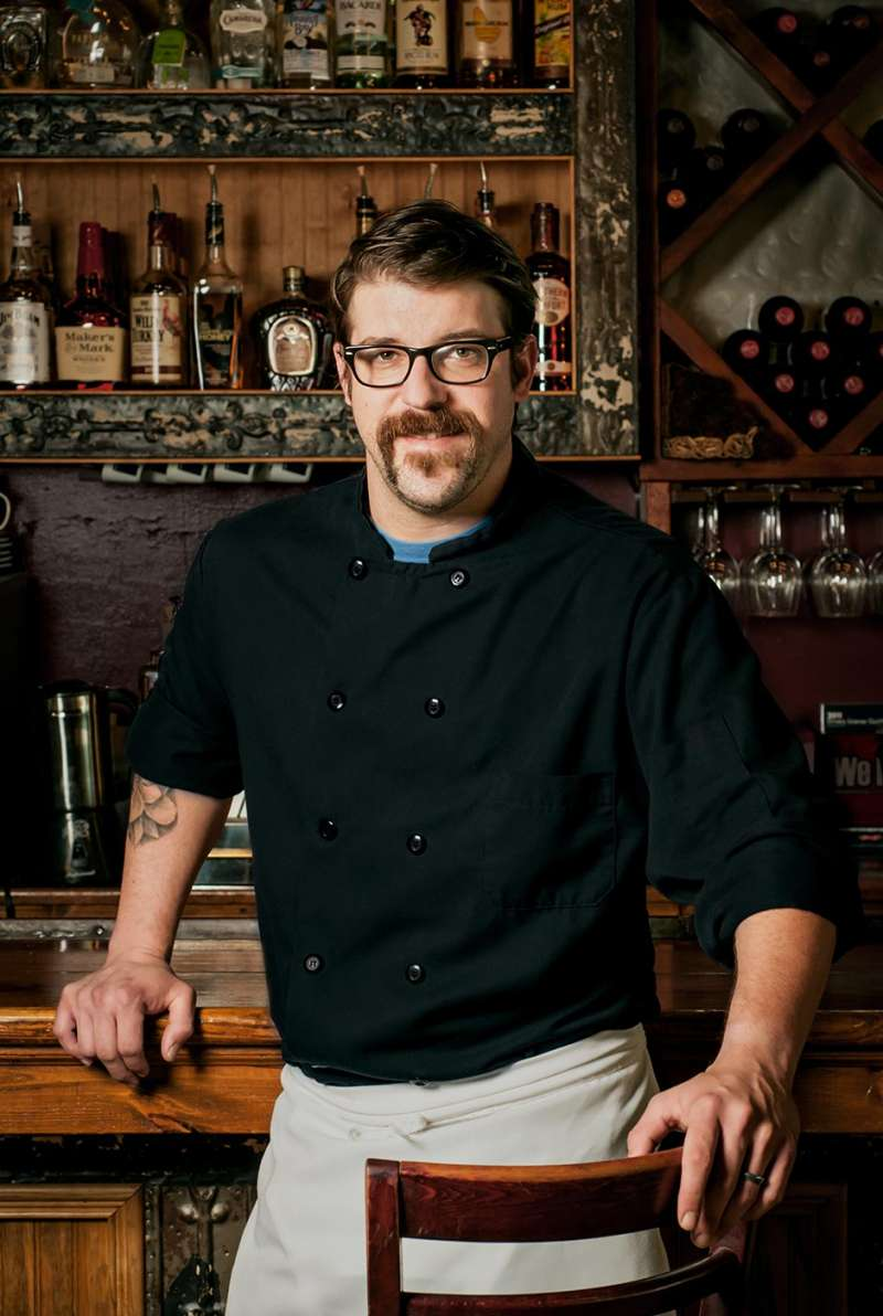 Portrait of a bistro chef standing with a classic restaurant bar in background.
