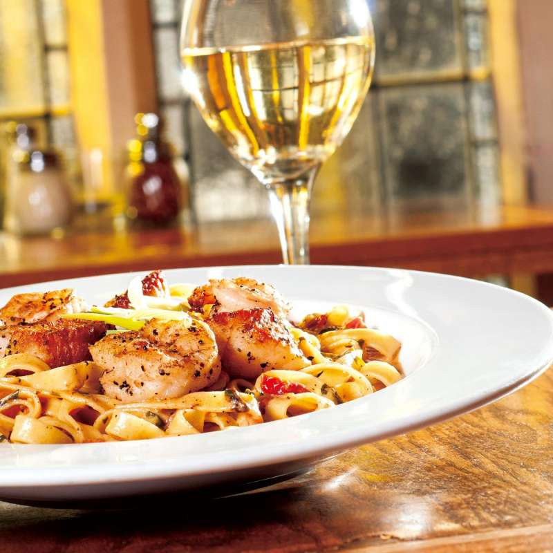 Food photography featuring a steaming charmaign fettuccine and white wine.