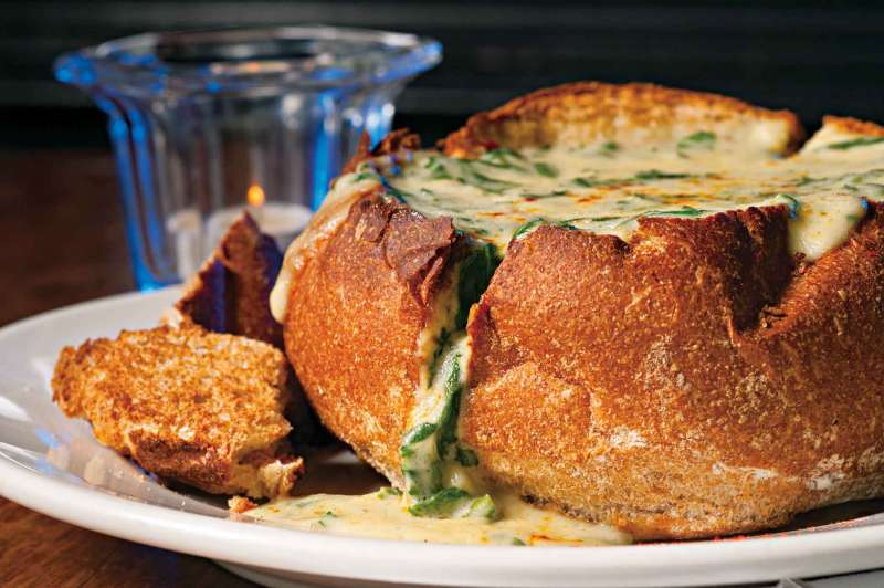 Cookbook photography of a spinach artichoke dip melting over a toasted bread bowl.