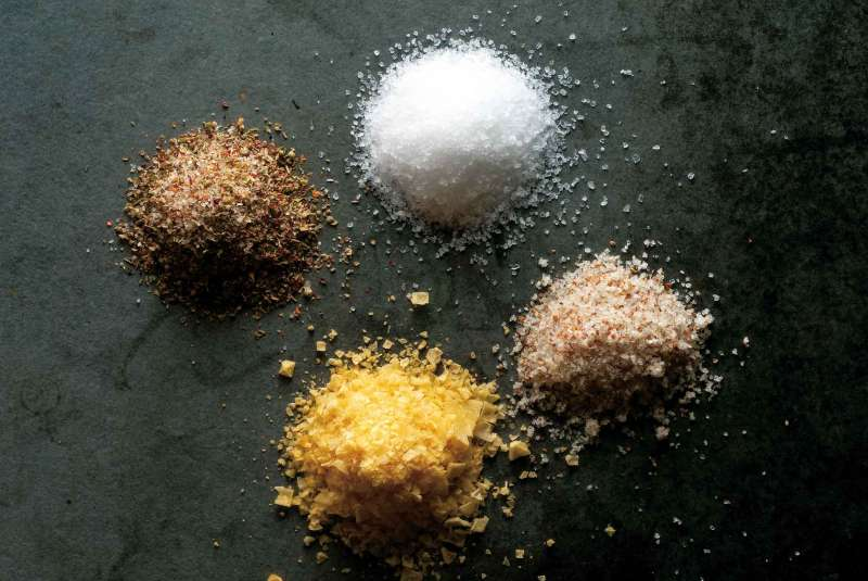 Photograph showing various types of salts on a dark background.