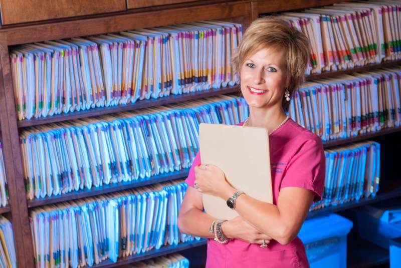 A dental assistant poses for a portrait in front of the office filing system.