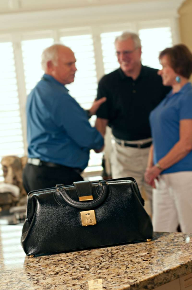 A doctor's little black bag sits on the table with doctor and patients in the background.