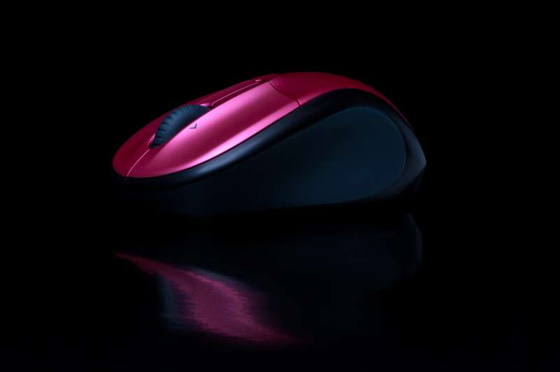 Beautiful electronics product photo showing a red and black mouse on a glossy reflective surface and black background.