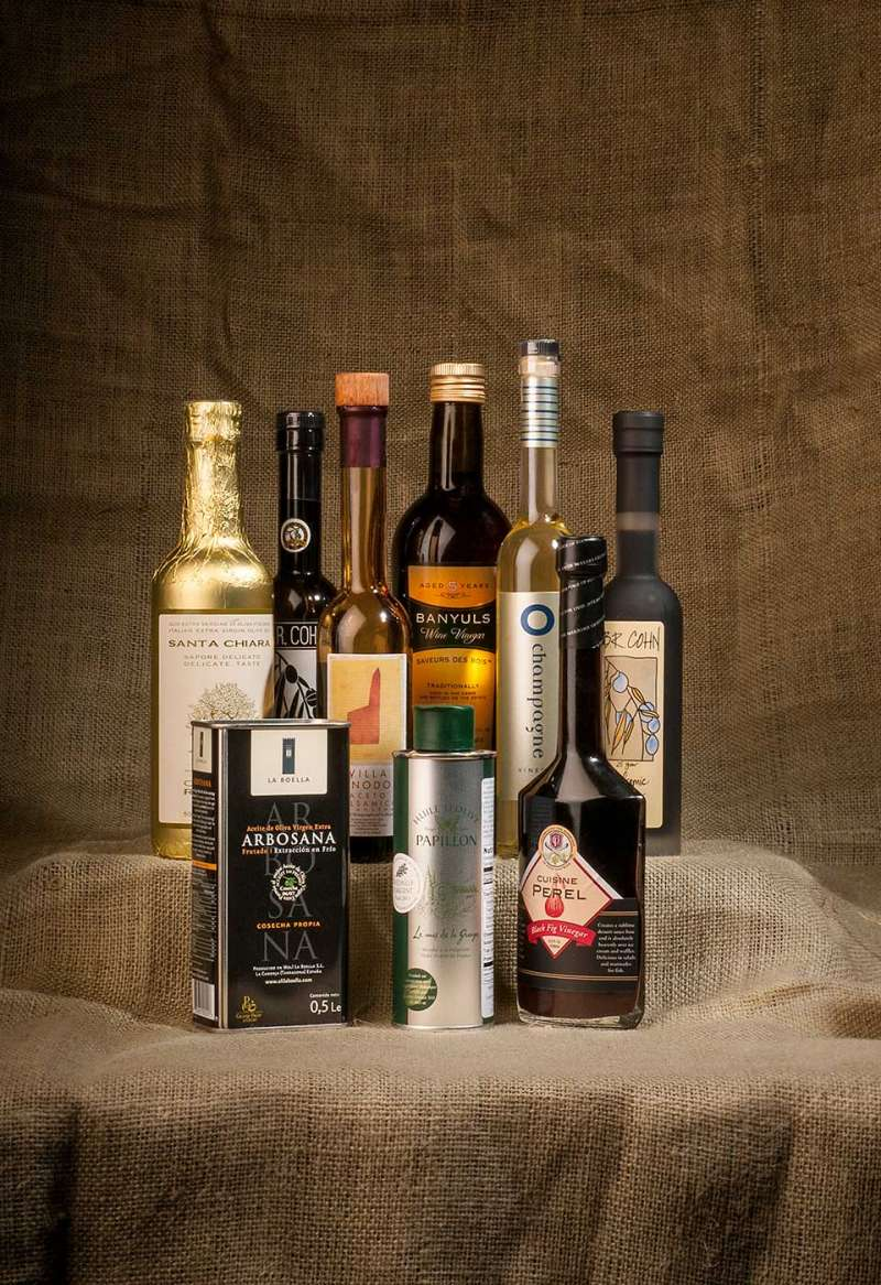 Food product photography showing various cooking oil and vinegar bottles against a burlap background.