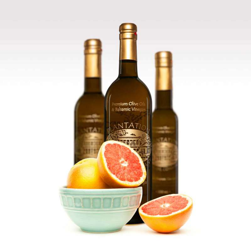 Food product photography of three olive oil bottles standing behind a bowl with one whole grapefruit and one grapfruit cut in half on a white background.