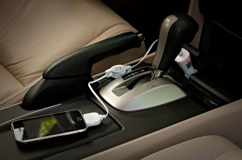 On location product photo showing a mobile phone charging cable in use inside a vehicle.