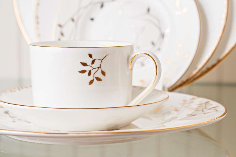 Retail product photography showing an elegant set of white tableware with gold ornamentation.