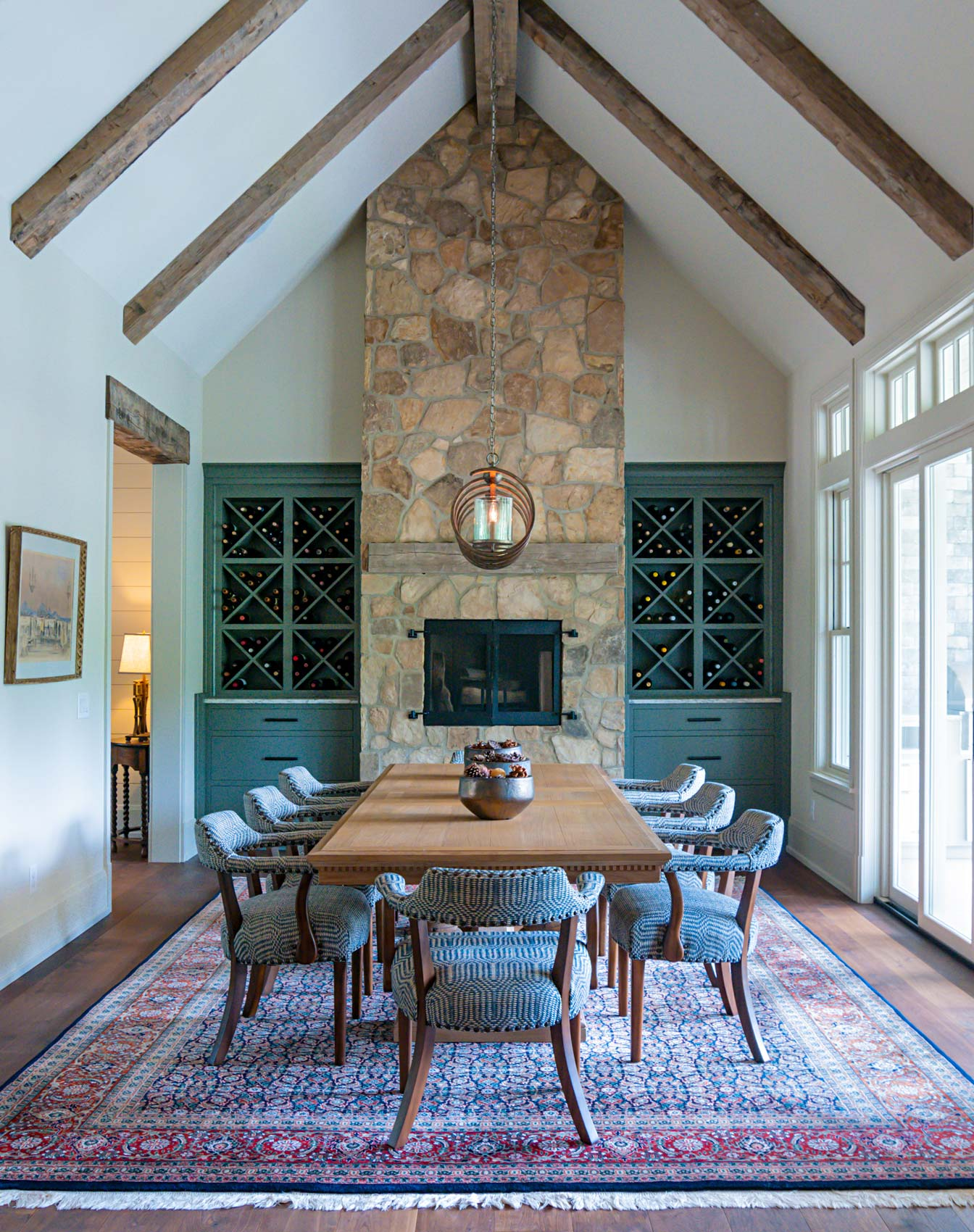 Photograph of a luxury home interior dinning area featuring vaulted ceillings, a stone fireplace mantle bordered by built-in wine racks. A long wooden table in the foreground.