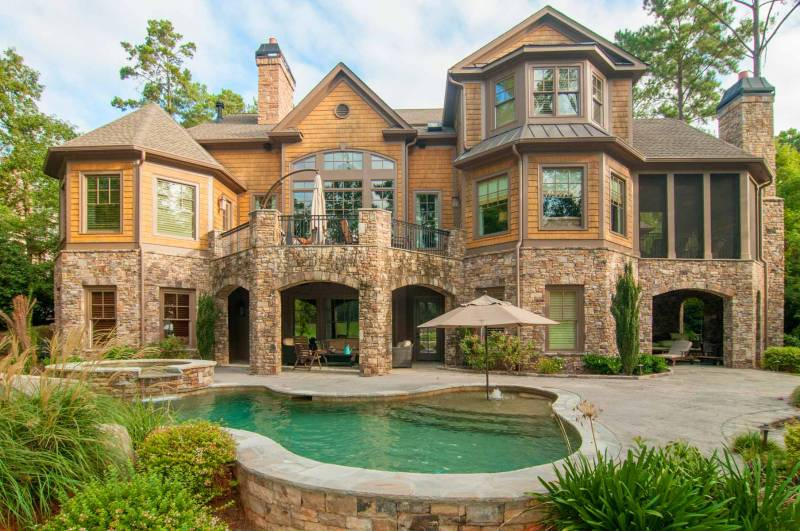 Residential photography ahowing the back of a very large house with swimming pool, stone decks and huge bay windows.