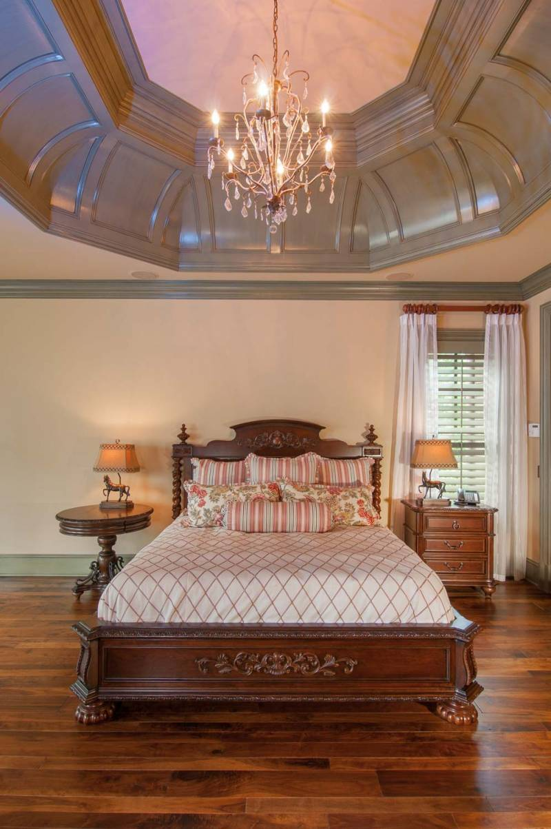 A gorgeous master bedroom with barrel ceilings and a chandalier above the wood frame bed.